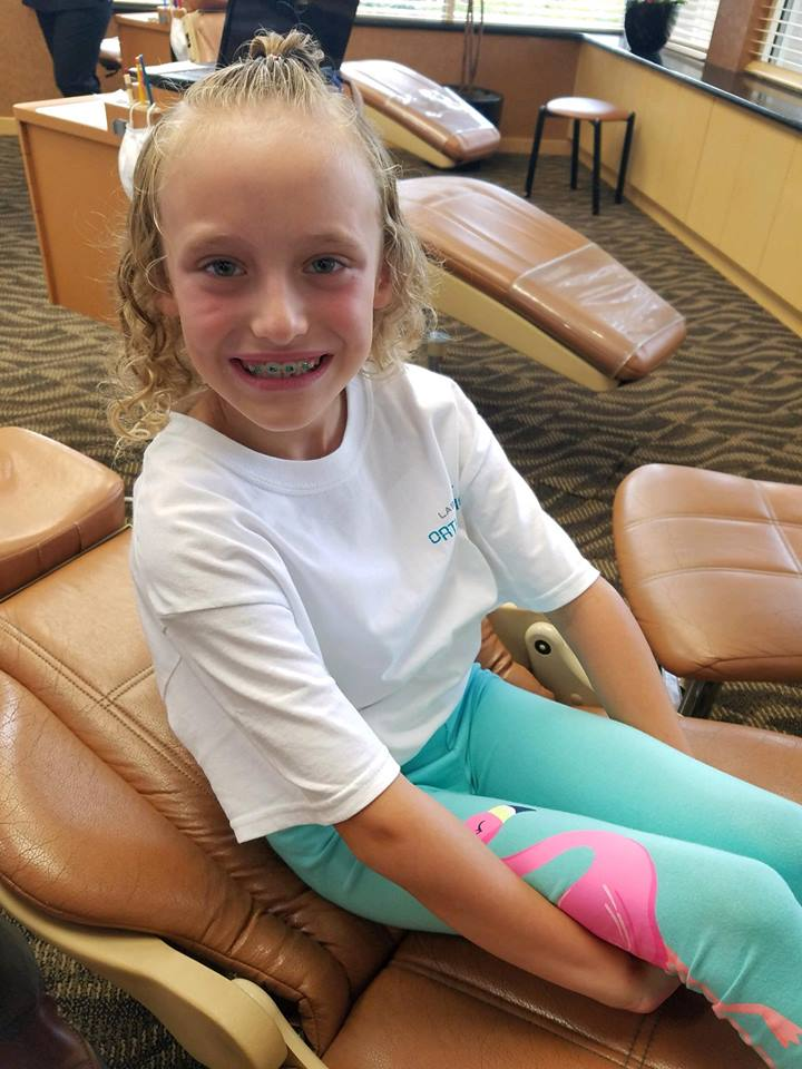litle girl with braces sitting in dentist chair