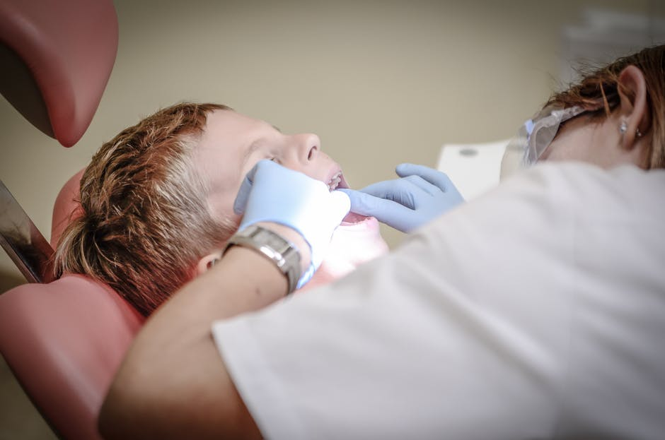 dentist working in the mouth of a little boy