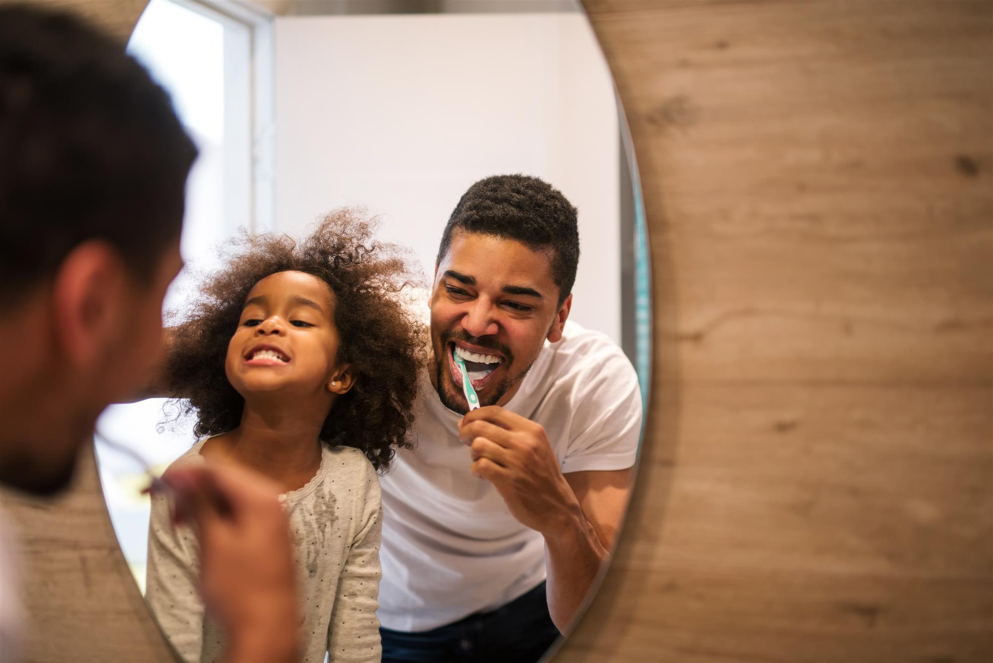 african amerian girl brushing teeth with dad