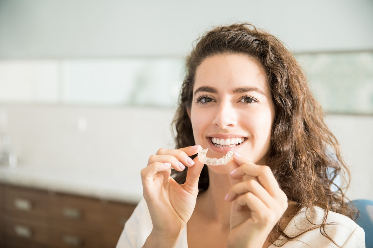 woman putting invisalign aligner tray into her mouth