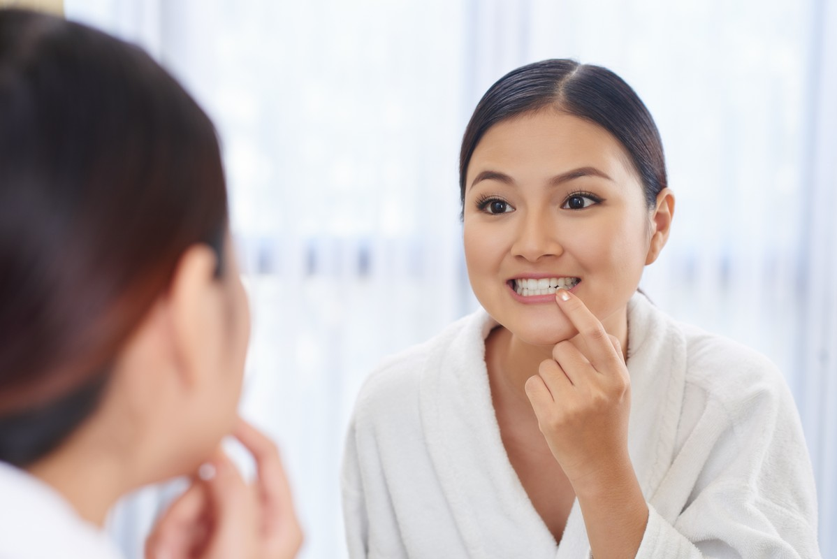 young asian woman looking at her teeth in the mirror