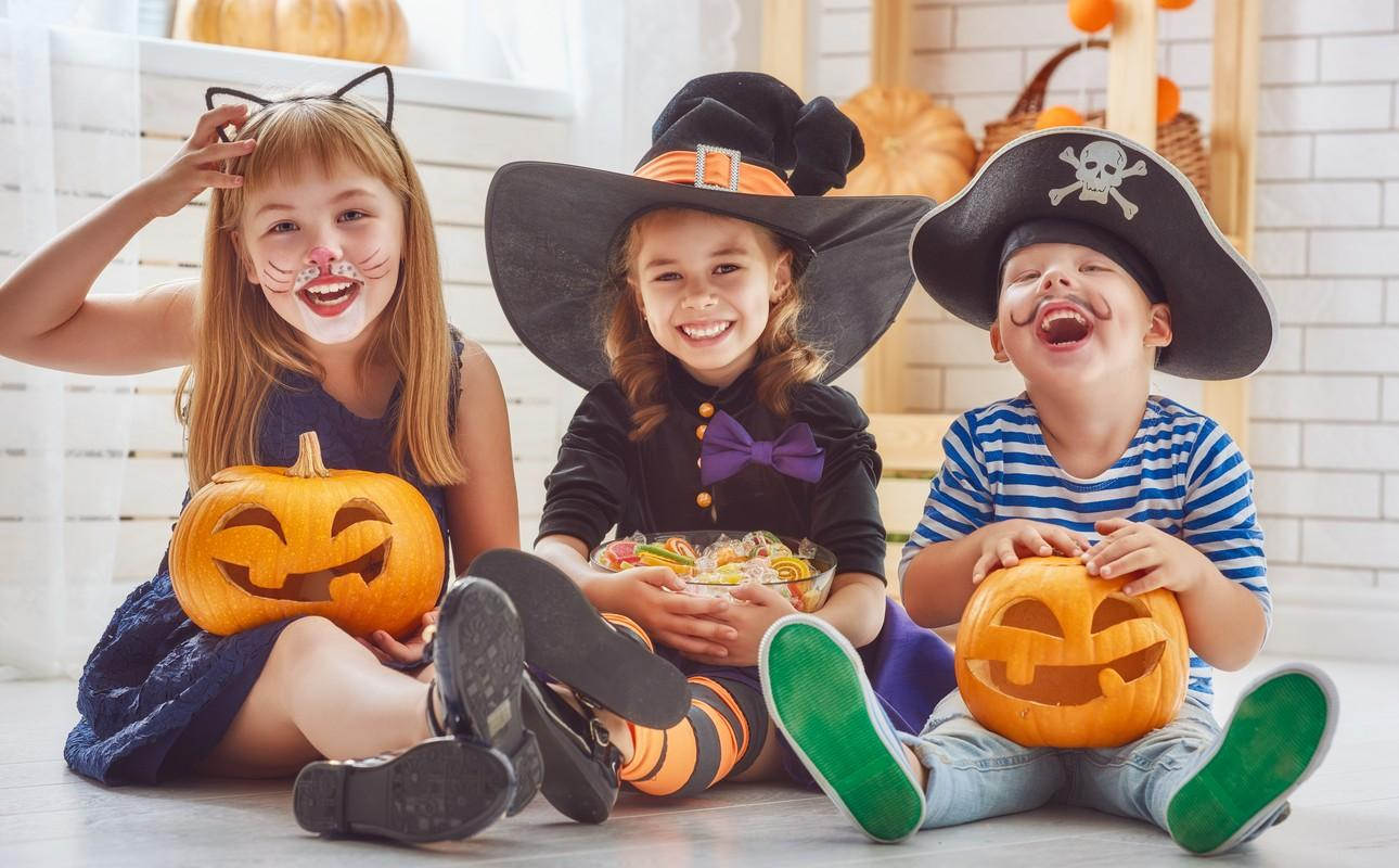 cheerful children play with pumpkins and candy