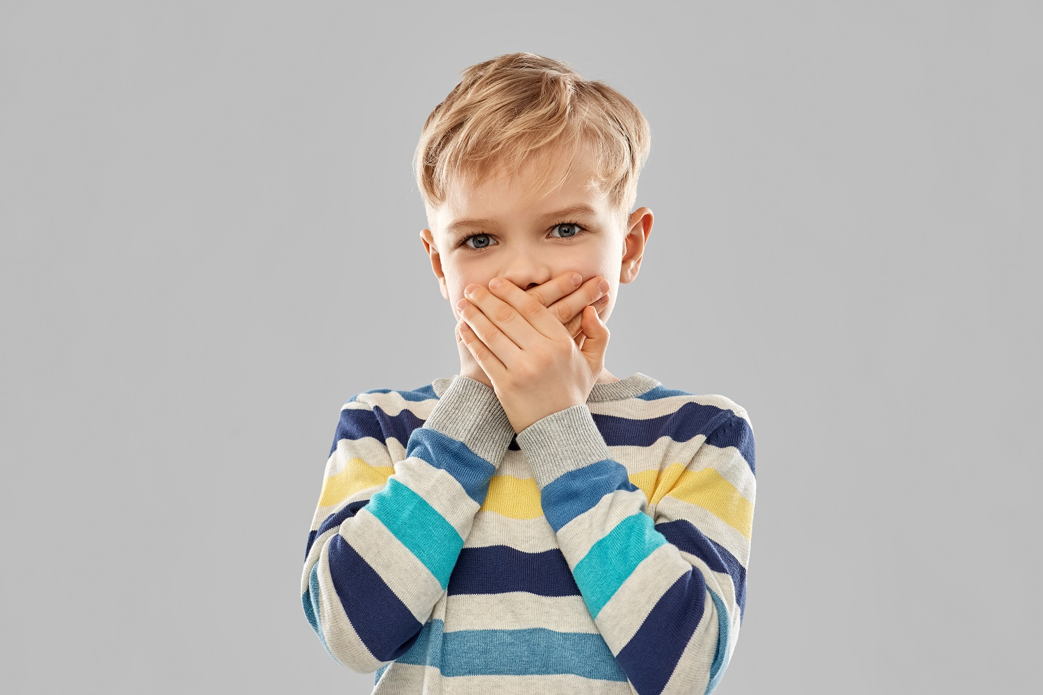 shocked little boy closing his mouth by hands