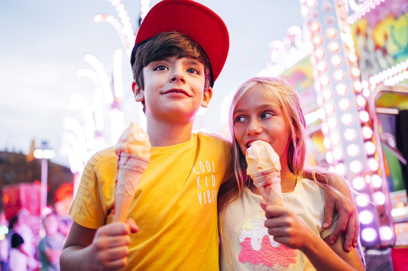 Smiling girl and boy walking eating ice cream