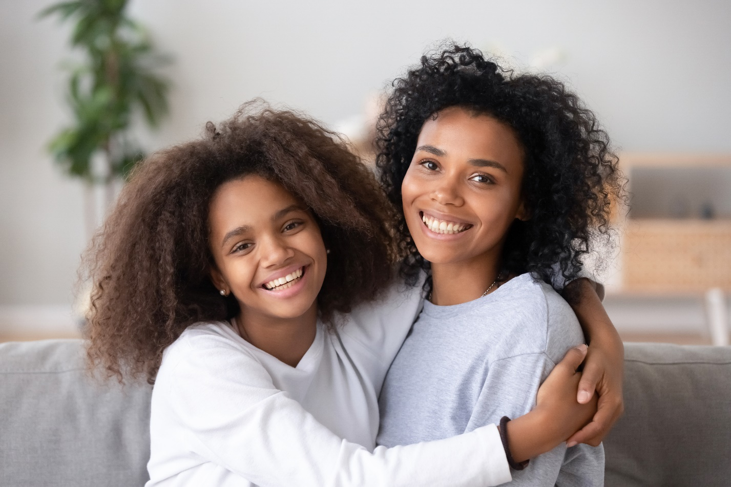 smiling black mixed race mom hug teenage girl bonding posing for portrait