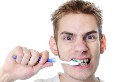 Young-Man-Brushing-his-Teeth-with-Braces